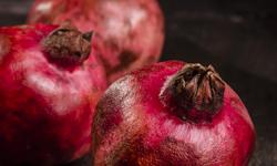 Three pomegranates on dark surface, negative space around